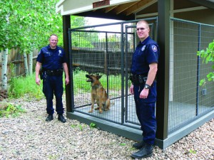 "The ""christening"" of K-9 Koda's newly built ""Kastle"" at the residence of Officer John Jones.  Officer Jones is on the left, Officer Brent Kieffer is on the right, and K-9 Koda sits in his new home looking at his ""Dad""."