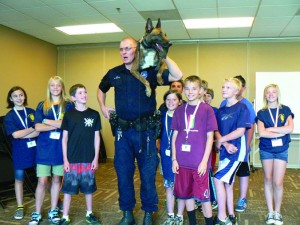 Taken at the Junior Police Academy held at Mission Hills Church in June 2014. The photo illustrates Officer Brent Kieffer and K-9 Sabor demonstrating advanced training technique utilized when K-9 must be placed in an overhead search area such as an attic.  Note that the Officer's right hand is on K-9 Sabor's back leg as it rests on the duty belt, an example of the high level of trust the canine has in the handler.